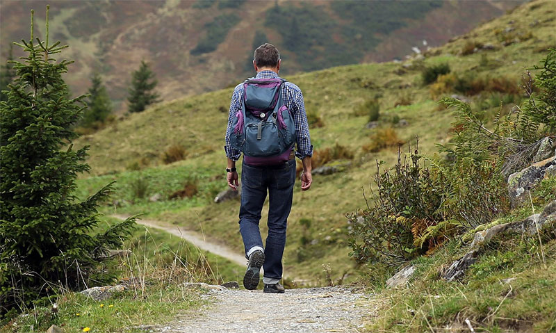man hiking with lightweight backpack