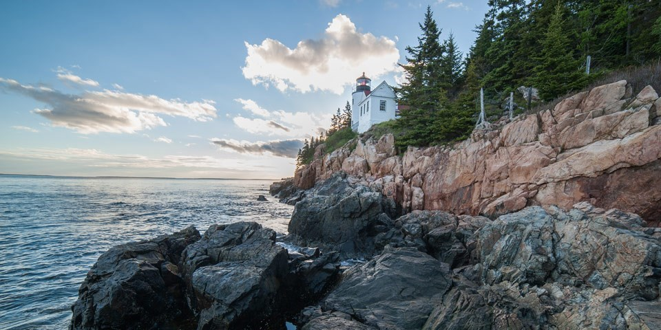 Lighthouse on the side of a cliff at Bass Harbor, with near cloudless blue skies and calm ocean