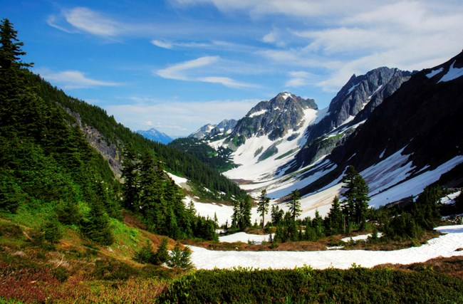 Oregon's cascade basin with a light covering of snow with blue skies and evergreens