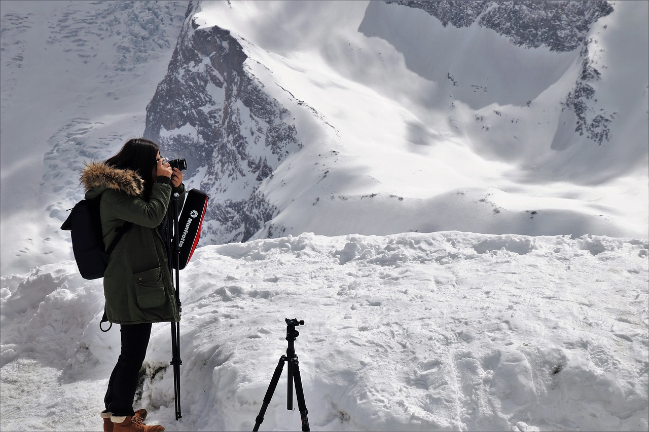 Woman taking pictures in the snow. The best camera backpack allows you to photograph nature in all weather conditions.