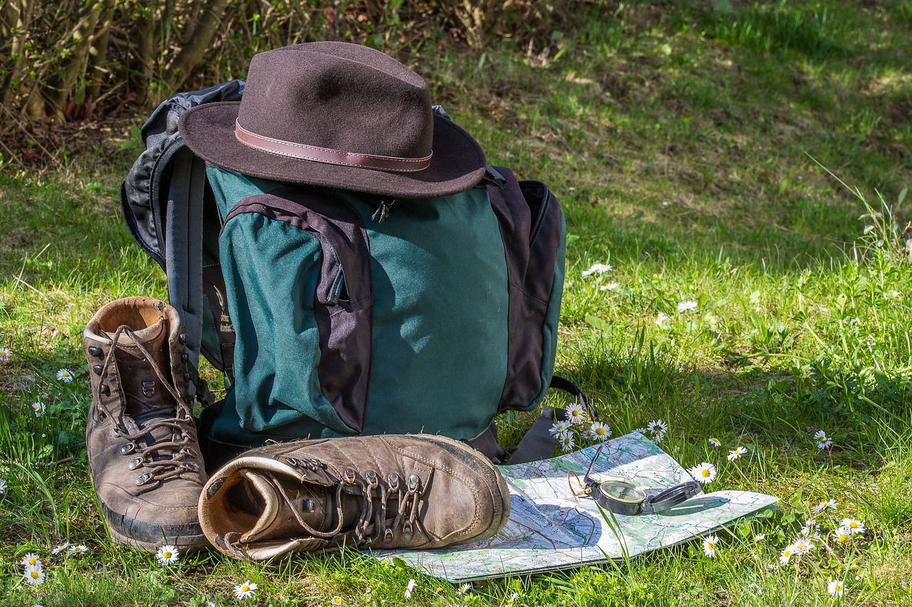 Hat, boots, map, and the best hiking backpack in the woods.