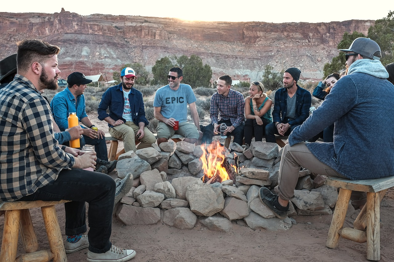 Men around a campfire. The best camping gear ensures a fun foray into nature.