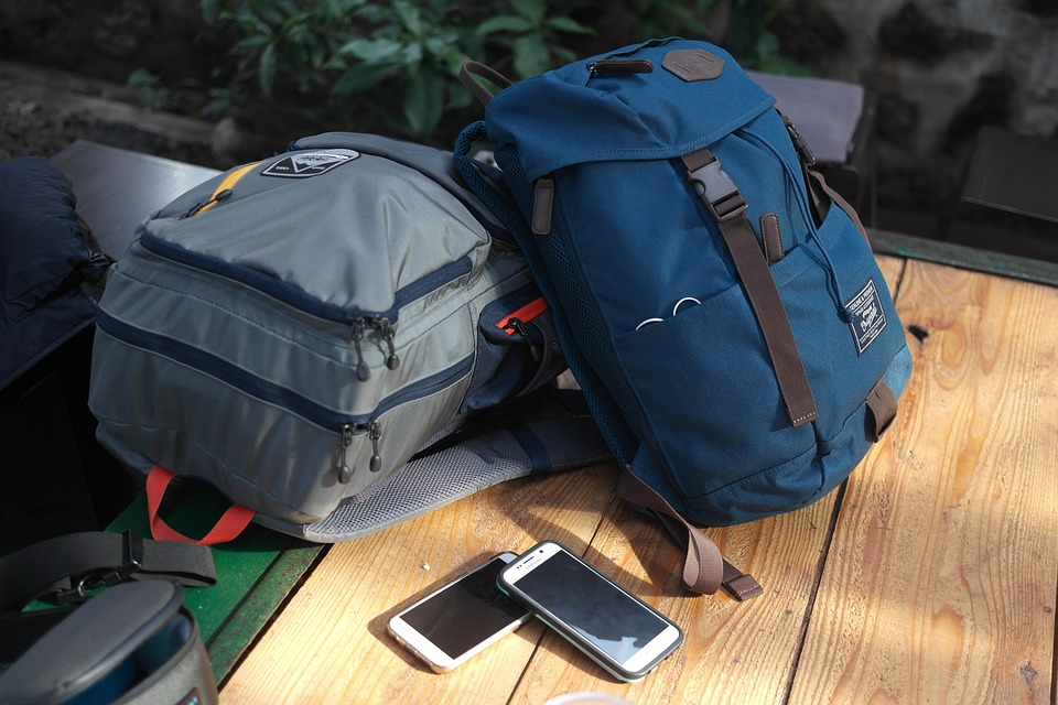 gray and blue travel backpack with two cellphones