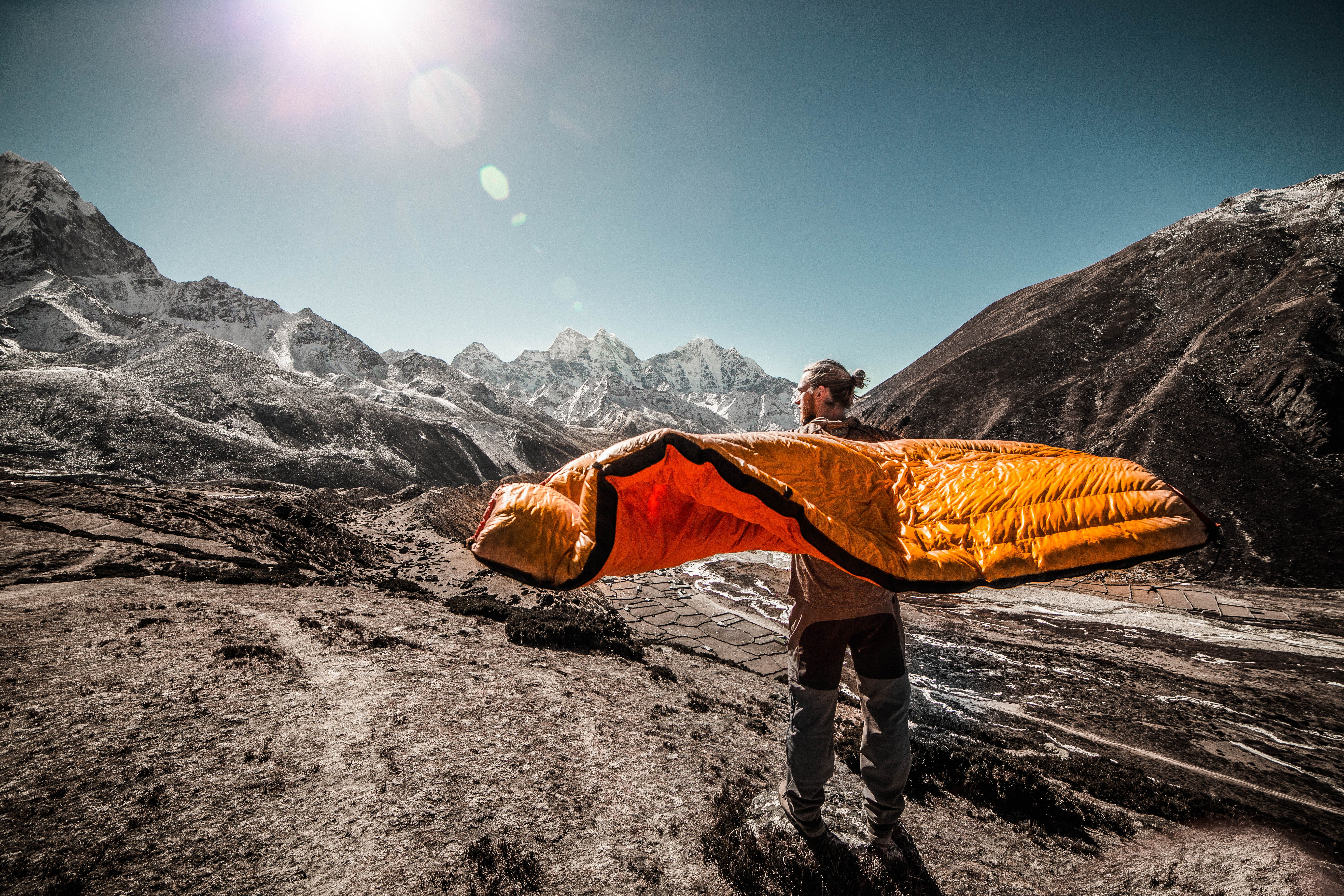 Man Standing on field between cliffs holding the best sleeping bag