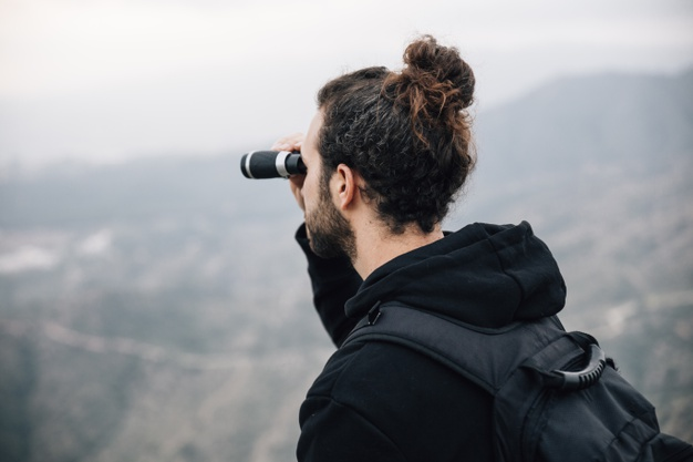 male hiker with his backpack looking mountain view through binocular