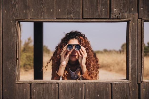 redhead woman looking through binoculars